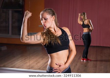 Half Body Shot of an Athletic Young Woman Showing her Arm Muscles Against her Mirror Reflection Background Inside the Studio.