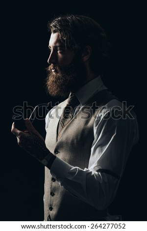 Half Body Shot of an Elegant Young Guy with Facial Hair, Wearing Formal Wear, Holding a Smoking Pipe While Looking to the Left of the Frame Seriously. - stock photo