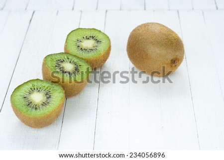 half cut kiwi fruits on white wooden table