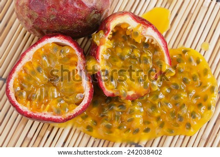 Half cut passion fruit with passion fruit juice on bamboo mat - stock photo
