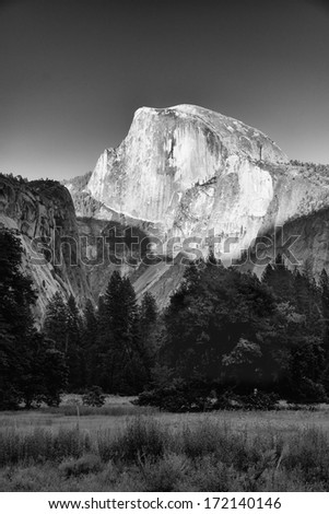Half Dome captured at sunset with the foreground casting shadows on the higher peak. - stock photo