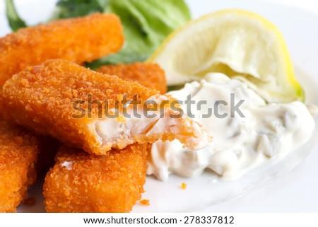 Half eaten fish fingers with lemon and tartar sauce. - stock photo