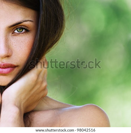 half face beautiful sexy girl with bare shoulders seductively posing with his hands touching face - stock photo