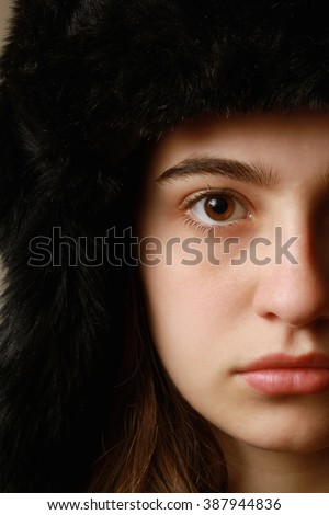 Half face of a girl with a Russian hat - stock photo