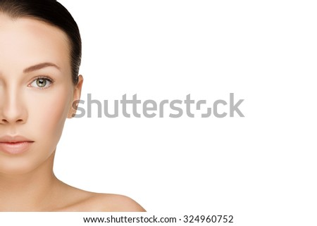 half face of beautiful young brunette woman with clean fresh skin with nude makeup looking straight. Closeup real photo - stock photo