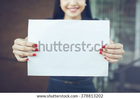 Half face of business woman holding an empty sign - ready to put text on