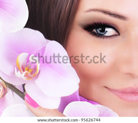 Half face of gorgeous young model, beautiful woman eye with fresh pink orchid flower,  part of female head, sexy girl with stylish look, spa and beauty background - stock photo