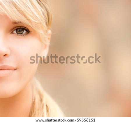 Half face of lovely girl close up on motley background. - stock photo