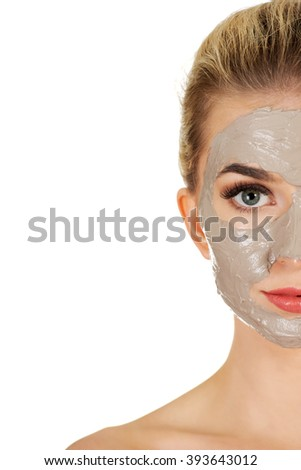 Half face of young woman with facial mask - stock photo