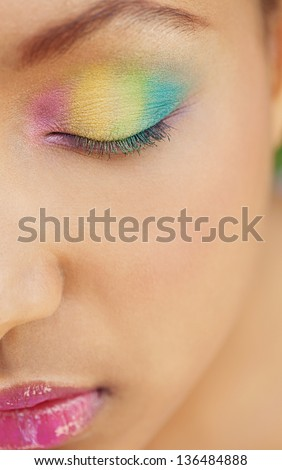 Half face portrait of a young african american girl wearing a rainbow eye shadow cosmetics and keeping her eyes closed.