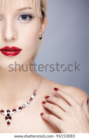 half face portrait of young beautiful blonde woman in necklace - stock photo