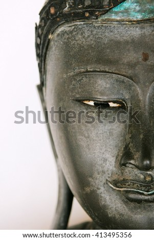 Half Face View of a Buddha Statue Isolated on a White Background - stock photo