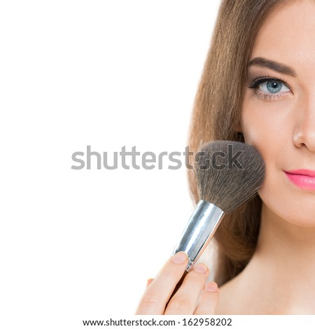 Half-faced portrait of a young woman with a make-up brush over white