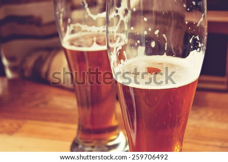 Half-full glasses of beer toned image. Glasses of beer on wooden table. Side view creative toned photo of man sitting at wooden table part view. There is free space in the left of table - stock photo