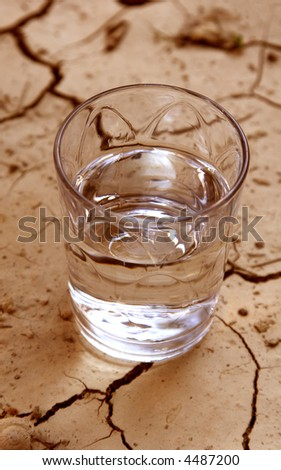 half glass of water on cracked earth - stock photo
