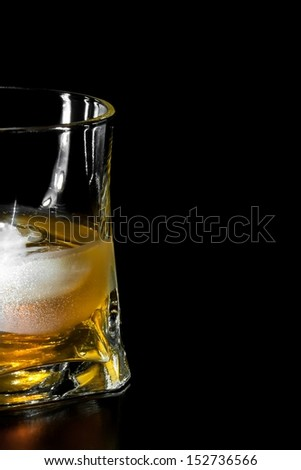 half glass of whiskey with ice  with space for text on black background - stock photo