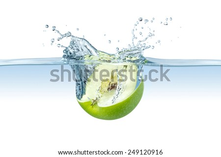 half green apple splashes into water - stock photo