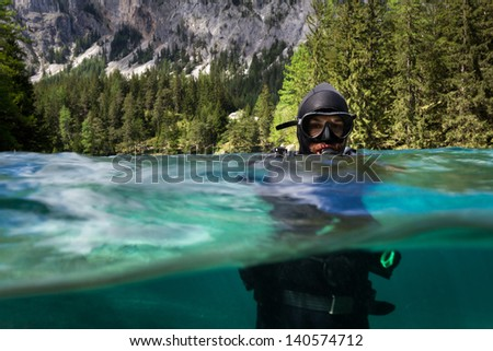 Half half photo of Scuba Diver in the lake Gruner in Austria with green water and Alps visible in the background. - stock photo
