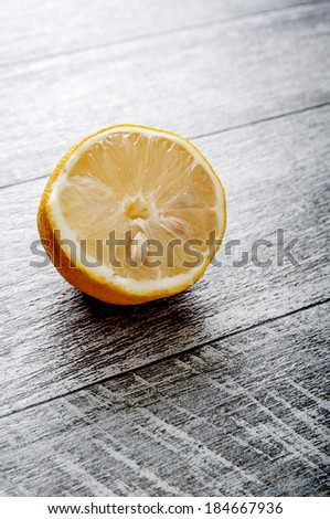 Half Lemon on old wooden table, backlit - stock photo