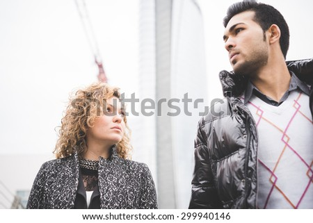 Half Length of a couple of handsome young caucasian and asiatic business man and woman overlooking posing in the street of the city - stock photo