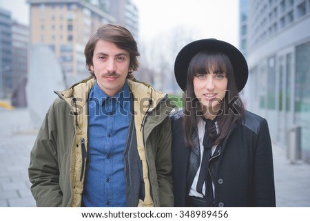 Half length of a couple of young caucasian man and woman posing in the streets of the city - carefreeness, friendship, love, youth concept