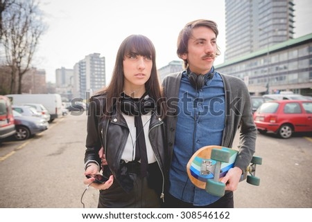 Half length of a couple of young caucasian woman and man with a skate and moustache posing trough the streets listening to music by technological device - carefreeness, friendship, love concept  - stock photo