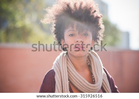 half length of a young beautiful black curly hair african woman looking in camera, pensive - pensive, serious, youth concept