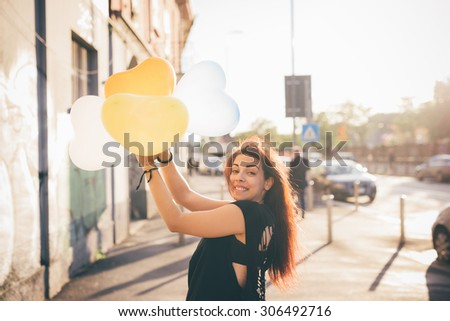 Half length of a young reddish brown hair caucasian woman playing in the street with baloon in shape of heart - youth, childhood, carefreeness concept - dressed with black shirt - stock photo