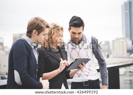 Half length of multiracial business people working outdoor in town. She is holding a tablet connected online, all looking down the screen - business, work, technology concept