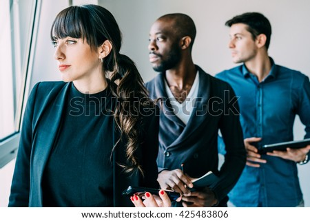 Half length of multiracial business people working posing indoor, holding technological devices, overlooking serious - seriousness, business, determination concept - focus on the woman - stock photo