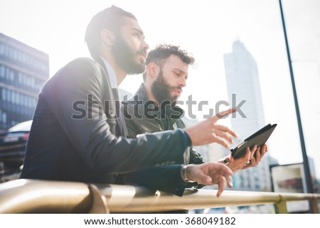 Half length of two young handsome caucasian bearded businessmen standing in city backlight, one holding tablet, other overlooking and pointing at something - business, technology, work concept - stock photo