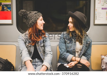 Half length of two young handsome caucasian blonde and redhead straight hair women sitting in the underground, looking one in the other eyes, chatting - friendship, transport, travelling concept