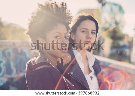 Half length of two young multiethnic friends outdoor in the city back light, looking in camera - friendship, woman power, serenity concept - stock photo