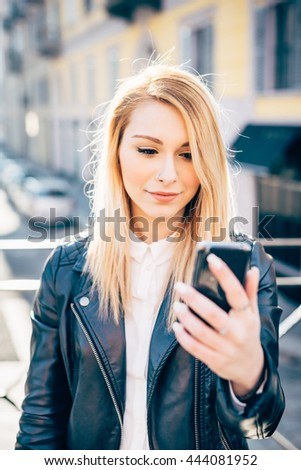 Half length of young beautiful millennial blonde hair woman in the city back light taking selfie with smart phone hand hold