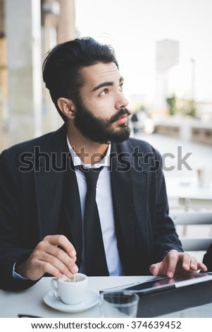 Half length of young handsome black hair caucasian modern businessman sitting in a bar, stirring the coffee, using a tablet and overlooking - business, working concept - stock photo