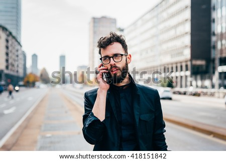 Half length of young handsome black hair caucasian modern businessman walking in the city talking smart phone smiling - business, working concept - stock photo