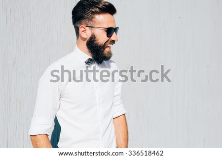 Half length of young handsome blonde caucasian modern businessman posing leaning against a wall, overlooking left, laughing - business, successful concept - stock photo