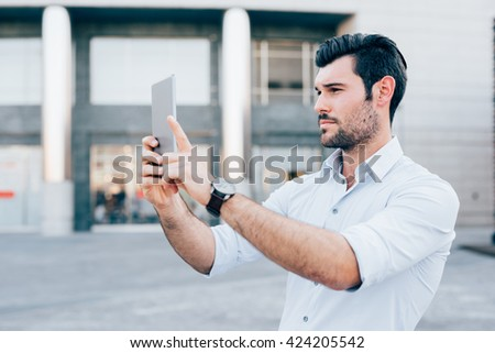 Half length of young handsome caucasian black hair modern businessman using a tablet taking photos - technology, social network concept - stock photo