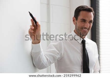 Half length portrait of a businessman smiling at camera and wrtiting on a blank billboard - stock photo