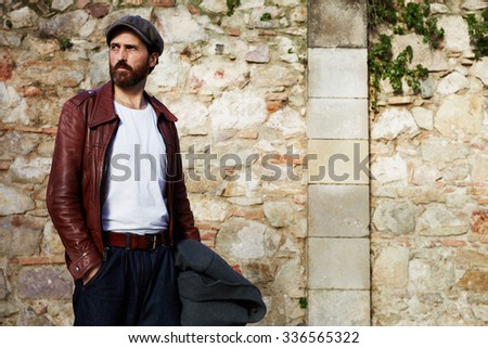 Half length portrait of a handsome adult bearded hipster man dressed in stylish retro clothes standing outdoors near street wall background with copy space for your text message or advertising content - stock photo