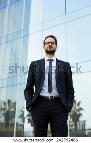 Half length portrait of a young businessman standing with his hands in the pockets near office skyscraper