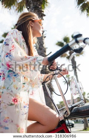 Half length portrait of a young fashionable woman sitting on touring bicycle on Miami street during summer holidays, attractive funky female posing with bike for excursions against palm tree - stock photo