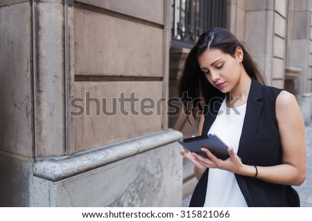 Half length portrait of a young female student reading digital e-book on touch pad computer on campus, beautiful woman watching video on her tablet while standing on the street in summer day  - stock photo