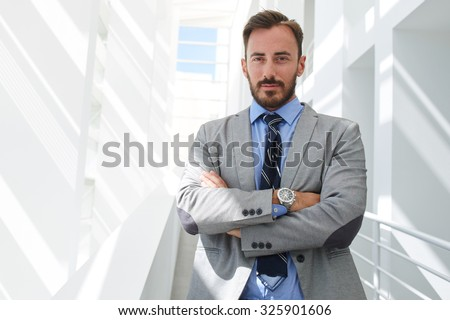 Half length portrait of a young handsome businessman with crossed arms standing in white hallway of his company, confident man managing director dressed in suit posing while resting after conference - stock photo