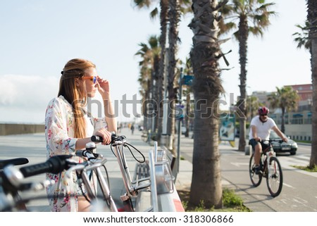Half length portrait of a young trendy beautiful female cyclist standing on parking for bicycles with bike against palm tree background with copy space area for you text message or advertising concept - stock photo