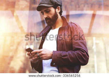 Half length portrait of adult bearded hipster man chatting on cell telephone during walking in urban setting, handsome male watching something on smart phone while standing on the street in autumn day - stock photo