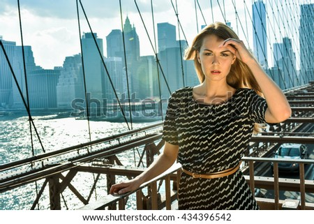 Half length portrait of an attractive blonde female model standing on the Brooklyn Bridge with city view on the background. - stock photo