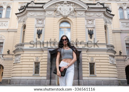 Half length portrait of an attractive female tourist standing on the background of antique building in the city center, young fashionable Caucasian model chilling after walk and having a good time - stock photo