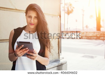 Half length portrait of an attractive latin business woman holding touch pad while standing on the street in summer day, female student reading news on digital tablet computer after lectures on campus - stock photo