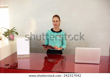 Half length portrait of attractive female entrepreneur standing at the cash desk with digital tablet in the hands, young office secretary or hotel receptionist holding touch pad gadget ready to serve - stock photo